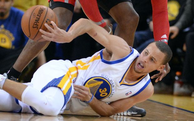The Golden State guard Steph Curry fights for the ball on the floor.