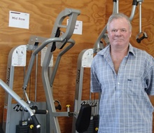 Nigel Bass standing next to the weights machines in the gym.