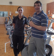 Brighid McCaffrey (left) completed a Masters degree and now works as a clinical exercise physiologist in the Health and Performance Clinic, for which Stacey Reading is Director. Gym equipment includes stationary bikes and weight machines.