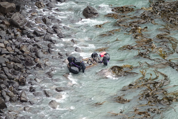 A helicopter lifted the wreck before dropping it closer to the cove's rocky shore.
