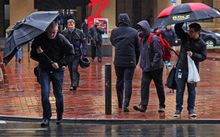 Commuters battle the horizontal wind and rain leaving Wellington Train Station.