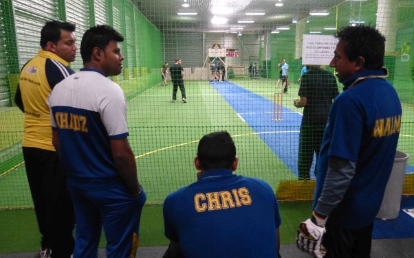 A team of Sri Lankans, including Nal Ariyawansa, watch a game of indoor cricket.