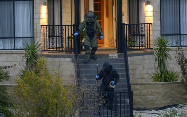 Officers wearing bomb suits raid a home in Greenvale, Melbourne, on Friday 8 May.