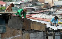 Residents along Manila Bay repair the roofs of their homes on May 10, 2015 in anticipation of Typhoon Noul as it approaches the northern Philippines.