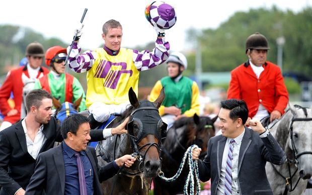 Jockey Mark Du Plessis celebrates after winning the Auckland Cup on Rock Diva at Ellersie.
