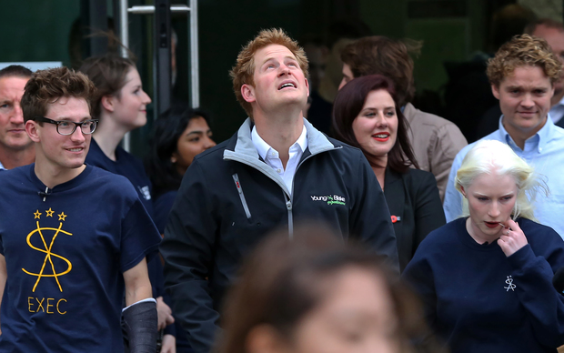 Prince Harry looking up at thunderous clouds about to downpour.