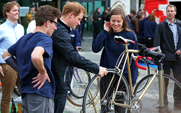 Prince Harry checks out his new bike, gifted by the Student Volunteer Army.