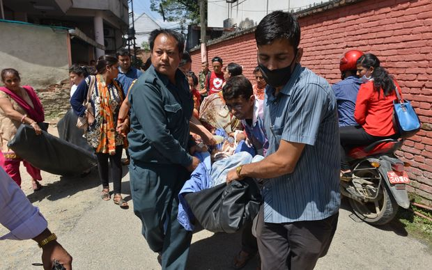 Nepalese patients are carried out of a hospital building following the 7.4 magnitude earthquake.