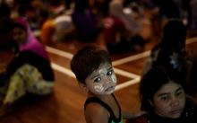 A Rohingya boy waits with other illegal migrants at a temporary detention center in Langkawi, Malaysia.