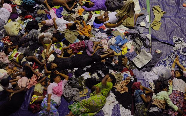 Rescued migrants sleep at a government sports auditorium in Indonesia's Aceh province.
