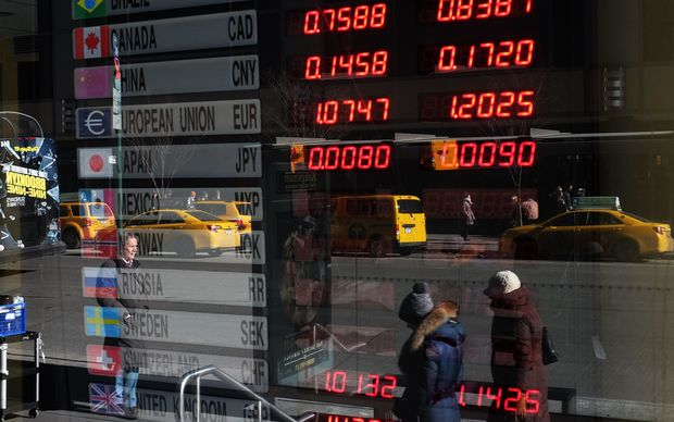 Foreign exchange rates displayed in a bank window.