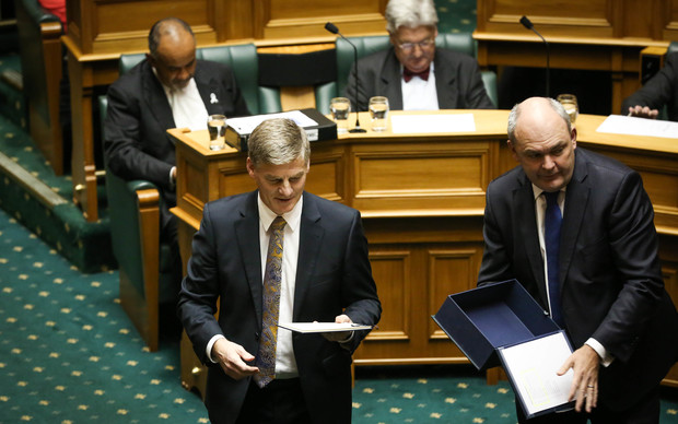 Bill English (left) and Steven Joyce handing out the Budget to parliament members in the house.