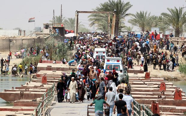 Residents of Ramadi who fled after the fall of the Iraqi city on Sunday cross a bridge on the outskirts of Baghad.