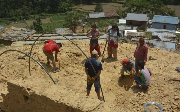 Residents of a village in Nepal's Kavre district work to build shelters for those left without houses. 23 May 2015.