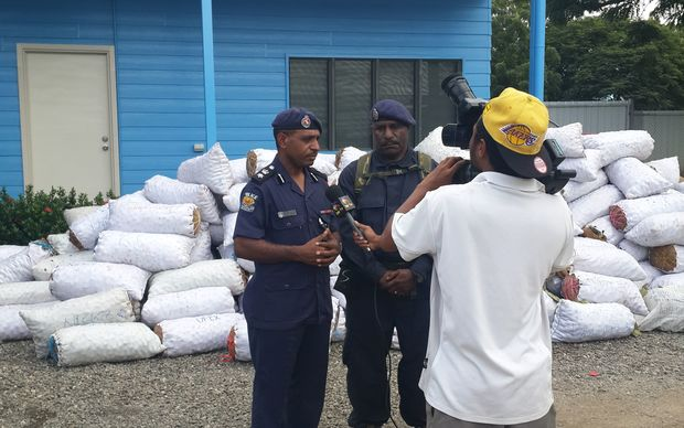 NCD Police Commander, Andy Bawa, and the Superintendent Operations pose for media in front of the confiscated betel nut
