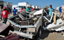 People survey a destroyed car in Ciudad Acuna, Mexico after a tornado ripped through the town.