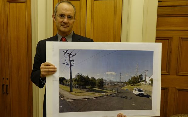 Labour's housing spokesperson Phil Twyford holds an image of a power sub-station in Auckland he says is on Crown land the Government plans for development.