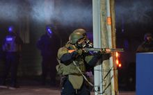 A state trooper aims his gun at protesters in Ferguson, Missouri, on 25 November, 2014 during a demonstration a day after violent protests and looting following the grand jury decision in the fatal shooting of  Michael Brown.