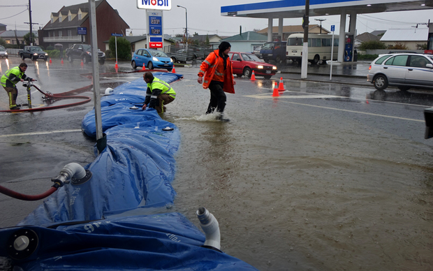 Emergency services pumping water out from flooded shops.