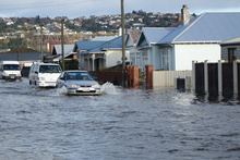 A car powers through floodwaters in south Dunedin on Thursday.