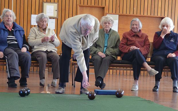 Five lades watch another club member make his bowl