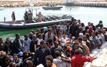 Libyan coast guards watch over illegal migrants, who had hoped to set off to Europe.