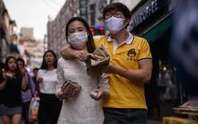 A couple wearing face masks walk on a street in the popular student area of Hongdae in Seoul.