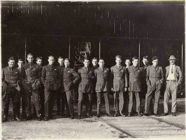 An image of 15 Flying School pilots in NZFS uniform standing in front of a plane in a hangar.