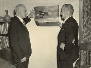 Image Leo and Vivian Walsh, 1940s, standing in front of a picture of  one of  their earliest aeroplane.