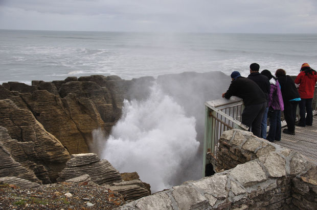 Tourists enjoy the main blowhole in action at the Pancake Rocks, Punakaiki