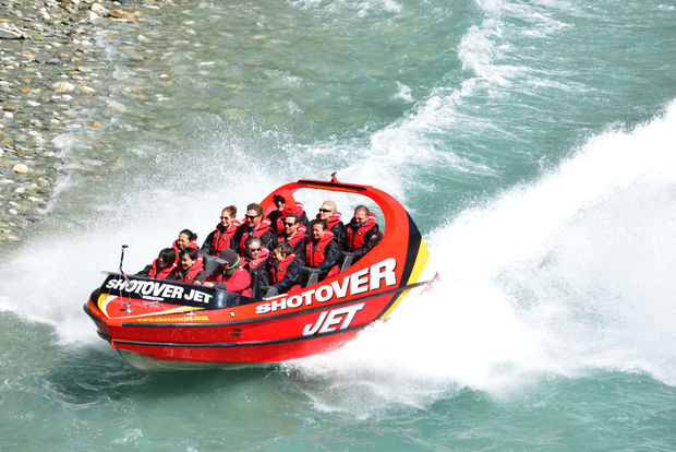 Tourists enjoy a high-speed boat ride on Queenstown