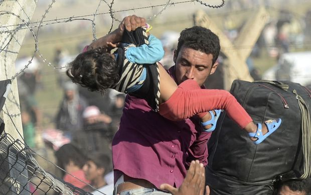 A man carries a girl as Syrians fleeing the war pass through broken down border fences to enter Turkish territory.