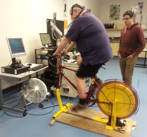 A photo of Colin Daley on an exercise bike with PhD student Adam Lucero