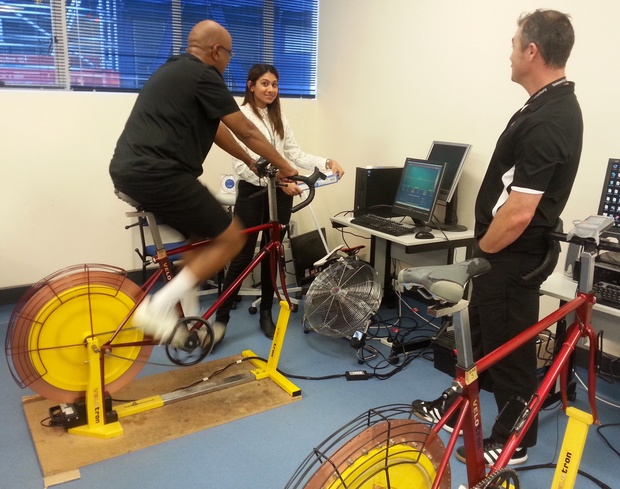 A photo of Ganesan Vadiveloo on the exercise bike with Shanggari Venugopal on the left and Kim Gaffney on the right