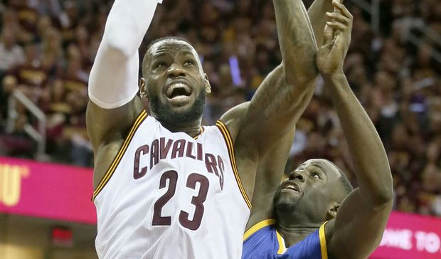 LeBron James, left, drives to the basket over Draymond Green