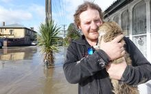 Aaron Fitton and his cat Iggy. Aaron's Waitotara house is knee high deep in water.