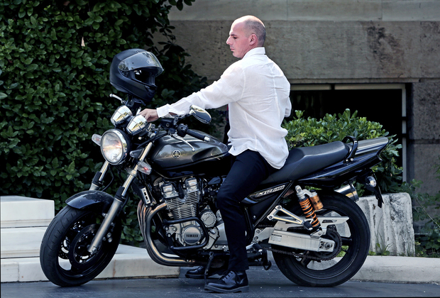 Greek Finance Minister Yanis Varoufakis arrives on his motorcycle for a cabinet meeting at the Prime Minister's office in Athens.
