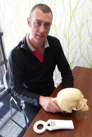 A photo of Simon Malpas with a wand used to wave over the device implanted in the skull