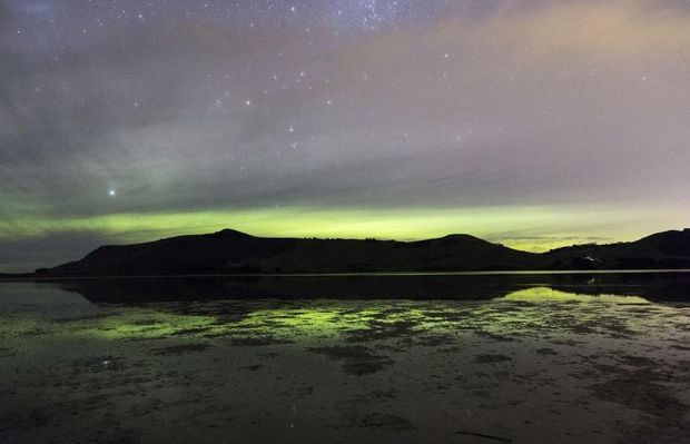 Sandymount on Otago Peninsula silhouetted by the Aurora.