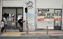 People walk past closed businesses in central Athens.