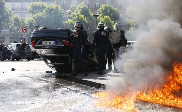 Smoke rises from a fire burning next to French CRS riot police standing near an overturned car as taxi drivers block Porte Maillot in Paris.