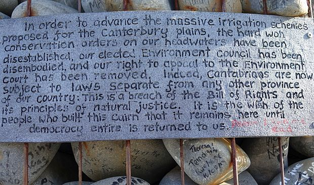Sign on cairn made of river stones outlining protestors thoughts