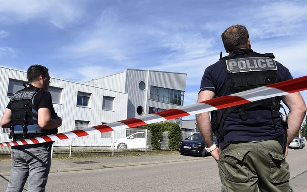 French police officers stand guard near a cordon outside the Colicom delivery service company in Chassieu near Lyon.