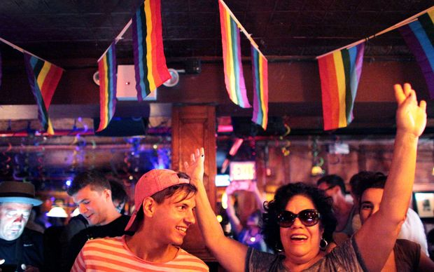 People celebrate inside the Stonewall Inn, an iconic gay bar recently granted historic landmark status in New York's West Village.
