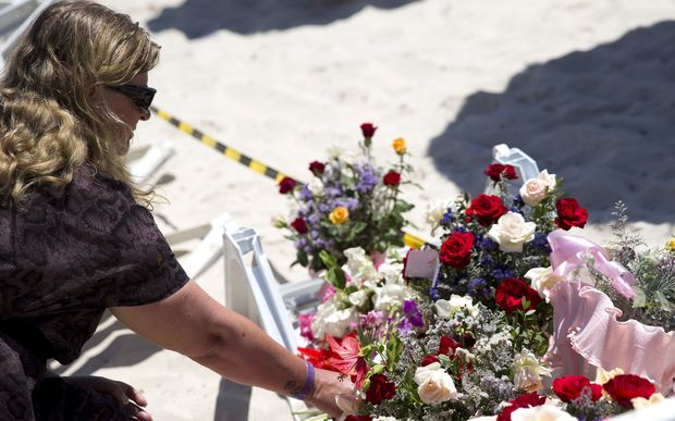 A woman lays flowers at the site of a shooting attack on the beach in front of the Riu Imperial Marhaba Hotel.