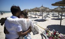 People react at the site of a shooting attack on the beach in front of the Riu Imperial Marhaba Hotel.