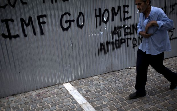 A man walks in front of a graffiti reading ''IMF go home'' in Athens.
