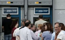 People queue at an ATM outside a National bank branch in a suburb of Athens.