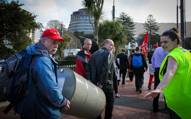 Protesters walk backwards from Parliament to the Wellington Train Station, highlighting the backwards move Kiwi Rail is making by replacing electric trains with diesel ones.