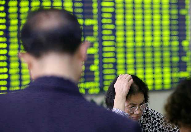 Concerned Chinese investors look at prices of shares (green for price falling) at a stock brokerage house in Nantong city, east China's Jiangsu province